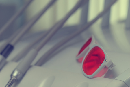 Pink glasses in white frame on the background of drills and wires in the dental office