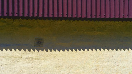 Shadow by the waves from the violet roof shingles on the yellow wall