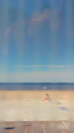 Blue sea and yellow beach through corrugated plastic transparent sheet in defocus Stock Photo