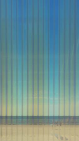 Blue sea and yellow beach through corrugated plastic transparent sheet in defocus Фото со стока