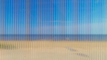 Blue sea and yellow beach through corrugated plastic transparent sheet