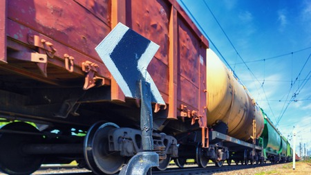 A freight train with freight wagons and cisterns rushes past the arrow against the blue sky in the summer