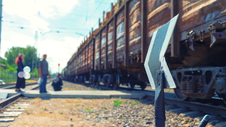 People wait in the summer at the arrow on the railway crossing when the train with freight cars passes