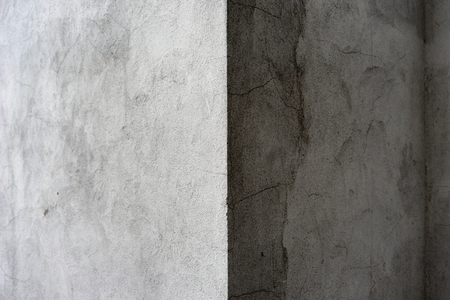 The corner of the gray house with cracks on the wall with lighted side and shadow