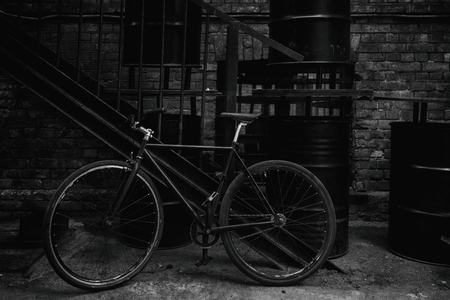 A bicycle stands near an iron staircase and metal black barrels