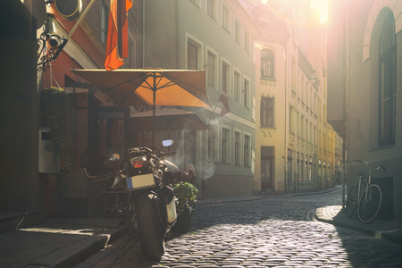 Motorcycle and bicycle at a street cafe under an umbrella on the street with cobblestone in the soft evening light. Riga, Latvia