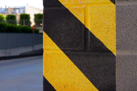 Yellow and black warning stripes on the corner of the gray building