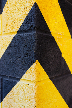 Yellow and black warning stripes on the corner of the building