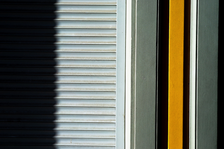 Lines of metal blinds on the wall with wooden boards with a shadow