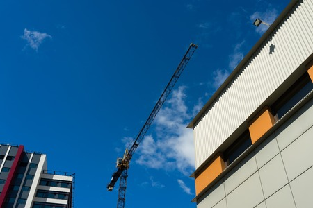 Construction crane against the background of new houses and blue sky Banque d'images