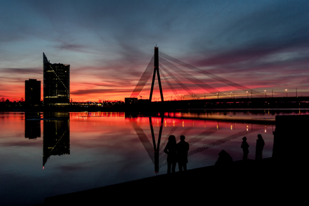 Sunset at the cable bridge on the Daugava River in Riga is watched by people silhouettes