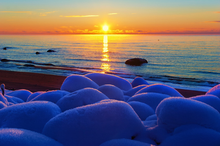 A blue sky is reflected on a white frost on the rocks in the sand of the Baltic Sea beach at sunset