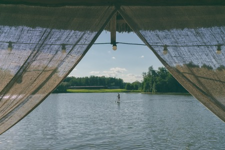 Curtains made of hand-woven fabric with light bulbs on the background of a lake and a forest in summer