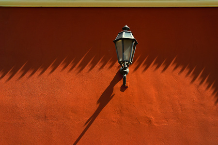 Street lamp on a painted red wall with long shadows in the old town
