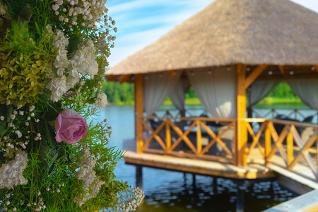 Rose and bouquet of flowers on the background of a summer bungalow on the lake
