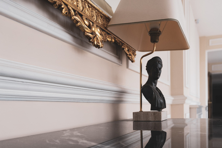 Decorative lamp with antique bust on a granite table under a gold frame of a picture in an interior