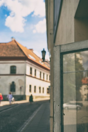 City life is reflected in an open window with a crack in the street of the old city of Vilnius Фото со стока