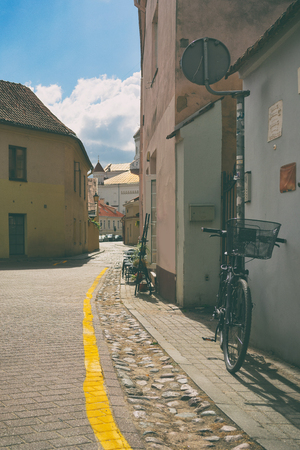 A street with a parked bicycle with a yellow stripe in the old city of Vilnius on a sunny summer day Фото со стока