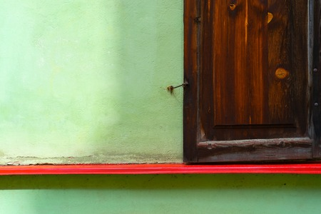 Wooden brown shutters with crochet on a green wall with a red sill line Фото со стока