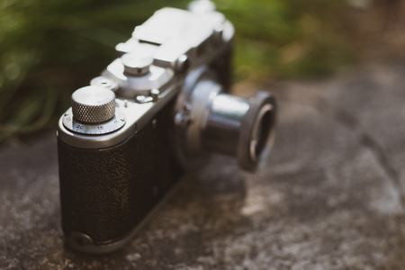 Vintage camera with chrome details in styling instant on stones in the garden