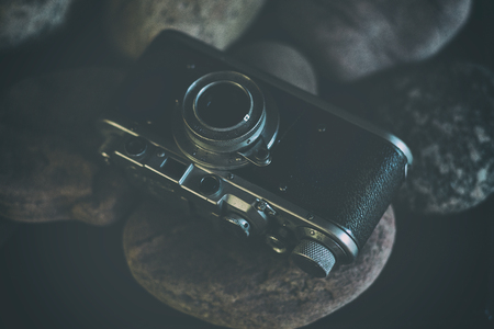 Vintage camera with chrome details on a background of stones in a dark key