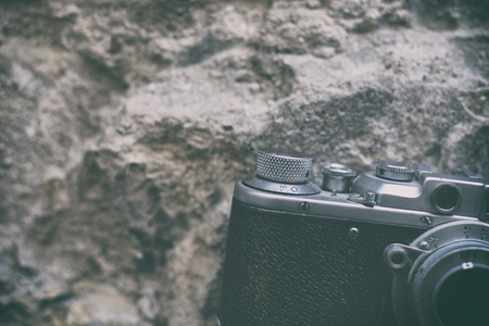 Vintage camera with chrome details on the background of the relief wall