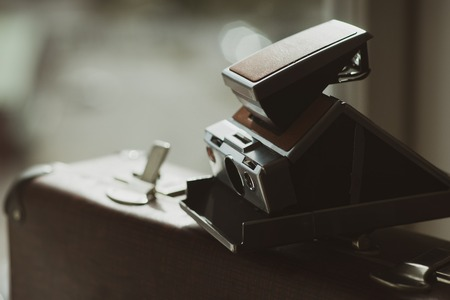 Vintage snapshot camera on an old suitcase with an open lock