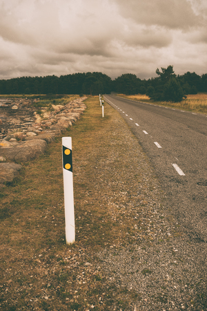 Road sign on an asphalt road near the sea in northern Europe on a cloudy summer day