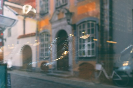 Reflection of the city with houses on the street and a bicycle in the glass showcases of the shoe store with mens shoes