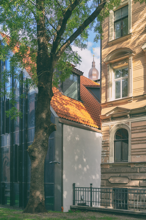 Courtyard in the historic old town of Riga with modern houses and a spire of the Dome Cathedral on a summer day