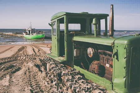 A green tractor with a motor and caterpillars on the sandy beach of the Baltic Sea helps to pull a fishing boat ashore