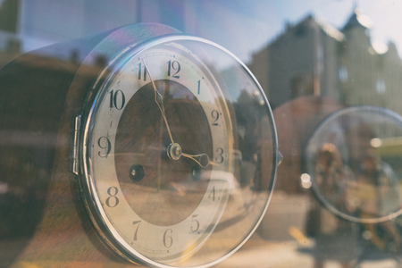 An abstract reflection of the life of the city with people and buildings in the antique clock behind the glass on a summer day