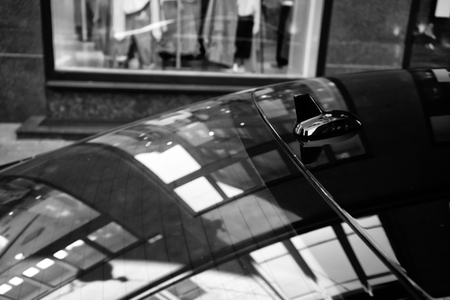 Reflection of the lines and shapes of the shop window on the glass and roof of the car. Black and white stylization Stock Photo