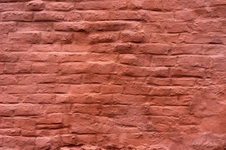 Painted red brick wall of an old building with uneven lines Stock Photo
