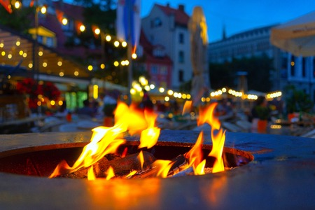 Fire burns with flames in the restaurants oven in Rigas square in the summer evening Stock Photo