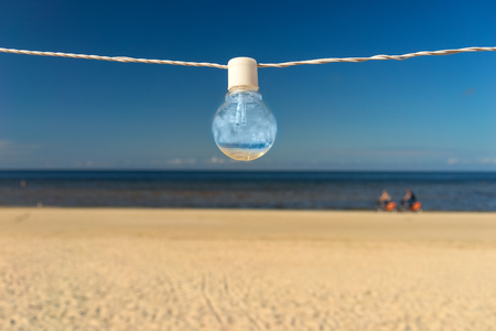 A bulb hanging on white on a wire on a sandy beach against a blue summer sky background