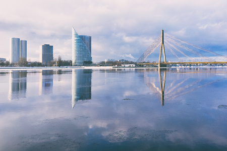 Skyscrapers on the embankment of Riga are reflected in the river Daugava with ice in the spring