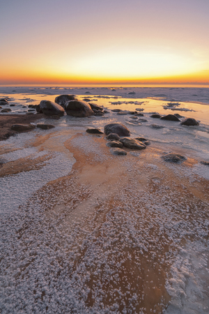 Sea frozen on a sandy beach with big stones in the Baltic Sea at the beginning of winter at sunset Фото со стока