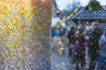 Snowfall at the Christmas market in the city on the background of a knitted scarf with a pattern Archivio Fotografico