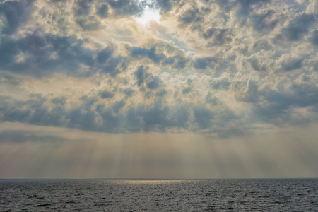Sun with rays through the relief clouds over the Baltic Sea and waves