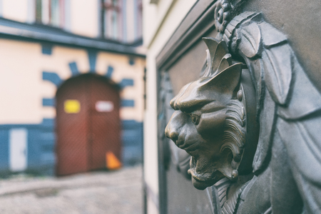 Bronze bas-relief of a cats head with a fountain on the wall of a historic house in the old city of Riga
