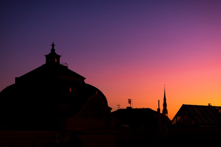 Profile of roofs with antennas and spiers of the city of Riga at sunset with birds in the sky