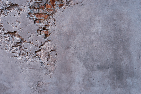 Textured gray embossed wall with fragments of old red bricks