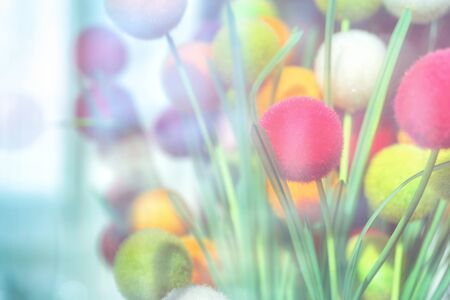 Abstract background of decorative multicolored balls on green stems behind glass