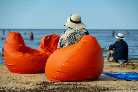 People in hats sit on orange soft chairs and look at people bathing on a hot day in the Gulf of Riga, the Baltic Sea Banco de Imagens