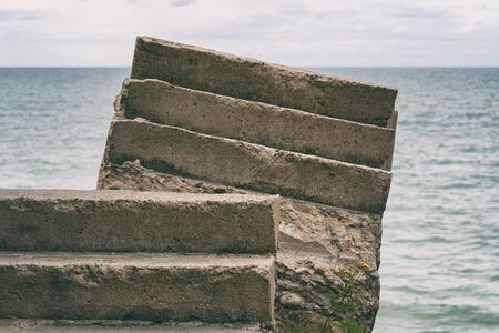 Concrete steps of the remains of the ruined fort against the background of the sea horizon with waves in the summer Stock Photo
