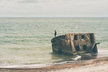 A man stands on the part of the destroyed military fort in the Baltic Sea Liepaja. Here were the military bases of Tsarist Russia and the Soviet Union. Stock Photo
