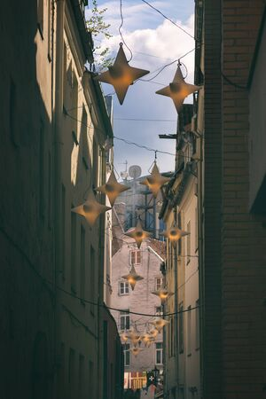 Narrow street with decorative lanterns and flags in the historical center of Riga