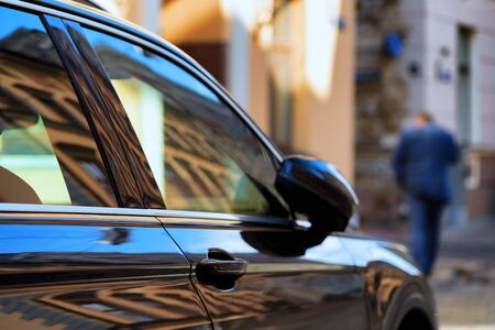 Parked car in the city center with reflection and a man in a suit