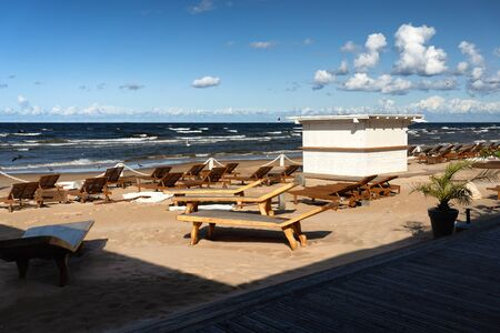 Summer cafe with tables on the sandy Baltic beach in Jurmala in early autumn on a sunny windy day. Latvia Reklamní fotografie